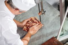 Carnicero Cutting Fresh Meat con la sierra de cinta Imágenes de archivo libres de regalías
