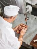 Carnicero Cutting Fresh Meat con la sierra de cinta Fotos de archivo