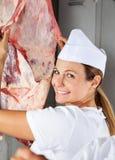 Carnicero de sexo femenino feliz Analyzing Raw Meat Fotografía de archivo libre de regalías