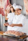 Carnicero de sexo femenino Giving Raw Meat en tienda Imagenes de archivo