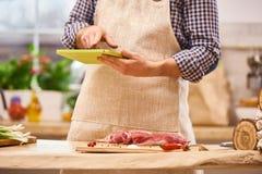 Carnicero del cocinero que prepara receta con la tableta digital en la cocina auténtica moderna imagen de archivo