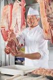 Carnicero Giving Raw Meat en el contador Imagen de archivo