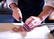 Carnicero que corta la carne de cerdo, cocinero que corta la carne cruda fresca, cocinero que cocina la comida en la cocina imagen de archivo libre de regalías
