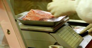 Carnicero que pesa la carne en la carnicería 4k almacen de metraje de vídeo