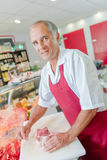Carnicero que prepara la carne de vaca común en tienda Foto de archivo