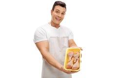 Carnicero que sostiene un paquete de tambores del pollo Foto de archivo libre de regalías