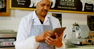 Carnicero que usa la tableta digital en la tienda 4k almacen de video