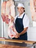 Carnicero sonriente Holding Meat Fotografía de archivo libre de regalías