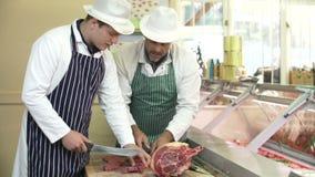 Carnicero Teaching Apprentice How para preparar la carne almacen de video