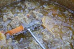 Carnitas - мексиканское сваренное шоу вытянул свинину варя в старом чайнике на на открытом воздухе огне - ломти мяса и апельсинов стоковое фото