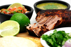 Carnitas. Pork roast cooked to make Mexican carnitas with fresh tortilla's' chunky tomato salsa and salsa verde and sliced limes Royalty Free Stock Photos