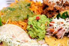 Carnitas With Rice And Refried Beans. Mexican style meal of Pork Carnitas soft tacos with refried beans, Spanish rice topped with fresh salsa verde and spicy Royalty Free Stock Photo