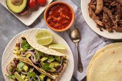 Carnitas tirati del porc con l'avocado e la cipolla rossa sulle tortiglii Alimento messicano fotografia stock