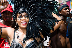 Carnival in black. Female masquerader in a black feathered headdress takes part in Carnival Tuesday celebrations in Port Of Spain Trinidad Royalty Free Stock Photography