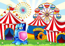 A carnival with a blue monster holding a shield Stock Photo