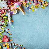 Carnival border with hats, candy and streamers. Carnival border with colorful party hats, candy and streamers on a texture blue background with copy space in