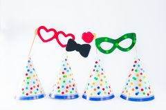 Carnival caps and funny masks on a white background isolated. Party tools and decoration. Happy birthday layout. Purim. Design. Concept. Select focus, Copy stock photography