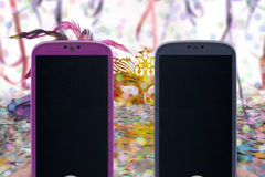 Carnival chatting and messaging. Female and male smartphones on Carnival background Royalty Free Stock Images