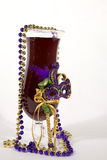 Carnival Cocktail. Purple drink in hurricane glass decorated with gold and purple beads and mardi gras mask on white background