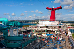 Carnival Conquest large cruise ship was docked at the coast of Jamaica. Panoramic view from the upper pool deck. Stock Photo