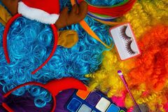 Carnival costumes. Wigs of bright colors, make-up, artificial eyelashes, decoration on the head. Preparation for the new year`s eve Stock Photo