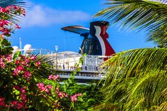 Carnival cruise ship Funnel view through palm trees and flowers. Ocho Rios, Jamaica - February 20, 2018: Carnival Vista cruise ship funnel viewed through a Stock Images