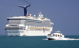 Carnival Cruise Ship and Tender in Belize. The Carnival Glory anchored of the coast of Belize, a popular western Caribbean port of call, as a tender shuttles Stock Photo