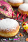Carnival donuts. On a dark wooden table with mask and confetti royalty free stock photos