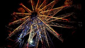 Carnival Ferris Wheel with lights at night. Families with kids celebrate summer.