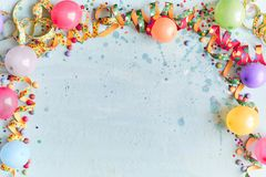 Carnival, festival or birthday balloon background. With colorful party streamers, candy and confetti making a border on a blue background with copy space