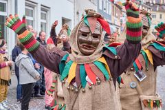 Carnival figure in a brown costume raises both arms. Street carnival in southern Germany - Black Forest stock photography
