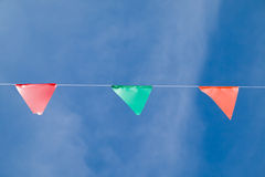 Carnival flag. Colored triangular flags on blue sky background Stock Photography