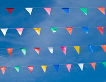 Carnival flag. Colored triangular flags on blue sky background Royalty Free Stock Photos