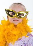 Carnival Girl. A young girl playing dress up with a yellow boa and gold mask royalty free stock photo