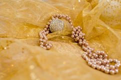 Carnival ornaments and jewelry. Carnival glamour background with a pearl necklace and gleaming ornaments in a pastele warm color royalty free stock image
