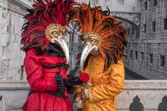 Costumed carnival-goers with red feathered mask standing in by the Bridge of Sighs during Venice Carnival Carnivale di Venezia. Carnival-goer in orange costume royalty free stock images