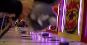 People smashing toy gophers in a game of whack a mole. Carnival goers hammer at moles in a whacking game lit up by neon stock footage