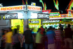 Carnival Goers Walk Among Fast Food Vendors Royalty Free Stock Photo