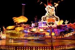 Carnival lights at night. Lights of amusement rides at a carnival at night stock images