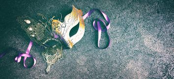 Carnival or Mardi Gras mask on textured grey. Gold butterfly design Carnival or Mardi Gras mask on textured grey background with copy space in banner format
