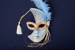 Carnival mask. Blue and gold feathered mask on a dark background Royalty Free Stock Photography