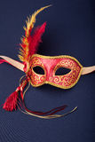 Carnival mask. Red and gold feathered mask on a dark background Royalty Free Stock Photos