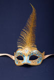 Carnival mask. Blue and gold feathered mask on a dark background Stock Photography
