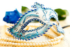 Carnival mask. Blue and white carnival mask on a music paper with blue rose on the background Stock Photo