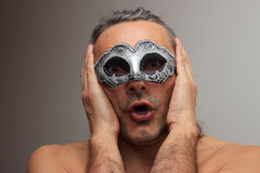 Carnival mask. Astonished man at the masquerade with silver mask Stock Photography