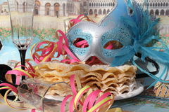 Carnival mask. Blue carnival mask with glitters and bleue feathers and  Venice in background, we can see two glasses and some pancakes Royalty Free Stock Image