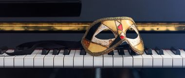 Carnival mask on piano keyboard, front view Stock Photo