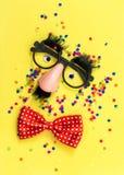 Carnival mask clown yellow background flat lay. Carnival mask clown on yellow background. Minimal flat lay stock image