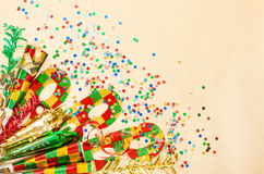Carnival mask, confetti, streamer. Holidays decorations. Over golden background Stock Photography