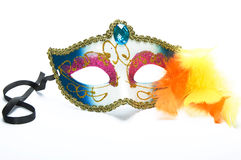 Carnival mask and feathers. Carnival mask in blue and pink with golden ribbon and glitter and yellow and orange feathers Stock Photos